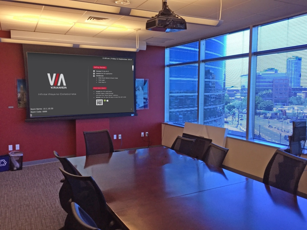 Conference Room With Vivitek Projector and Screen Innovations Motorized Screen. The VIA Campus Wireless Collaboration Device Home Page is Shown on the Screen.